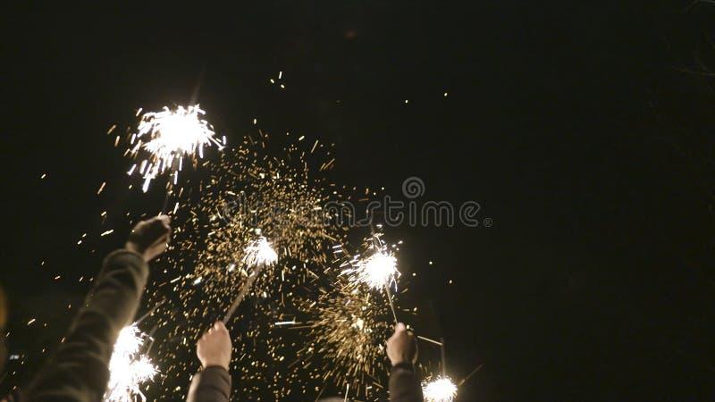 Le groupe de personnes célèbrent la nouvelle année sur la rue avec des cierges magiques action Heureusement et joyeux, les gens c photo libre de droits