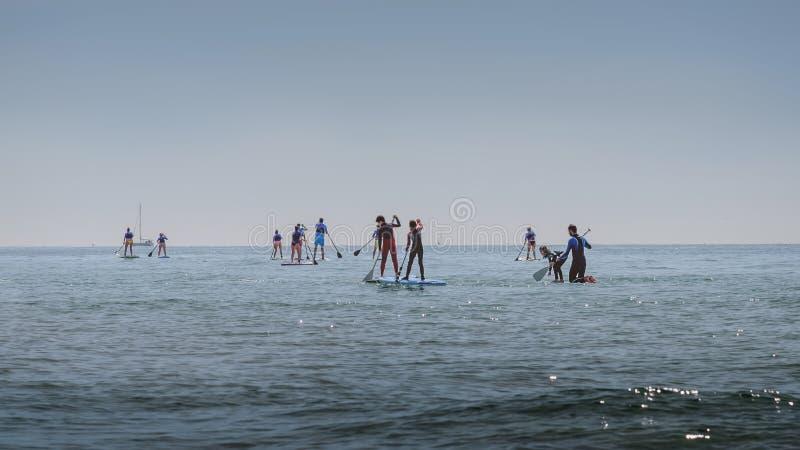 Le groupe de personnes dans le train de mer se tiennent barbotant Activité sportive extérieure Paysage d'ÉTÉ images stock
