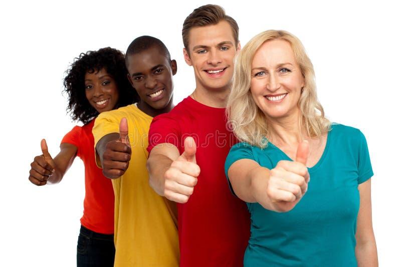 Le groupe de personnes de sourire avec des pouces lèvent le geste photo libre de droits