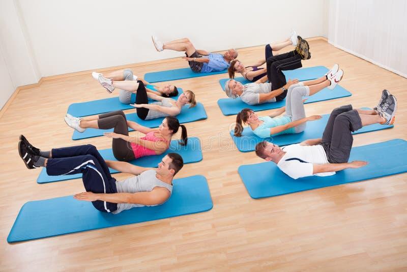 Le groupe de personnes exercsning dans un gymnase classent images stock