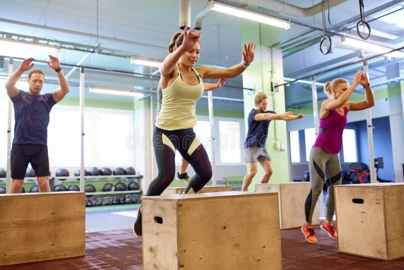 Le groupe de personnes faisant la boîte saute l'exercice dans le gymnase image stock