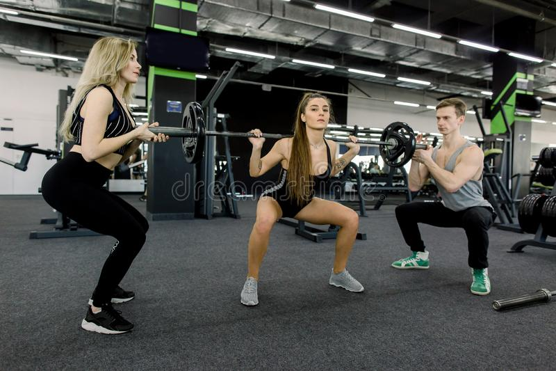 Le groupe de personnes fortes de sports font l'exercice de sport avec le barbell Les femmes attirantes et l'entraîneur musculaire photographie stock libre de droits
