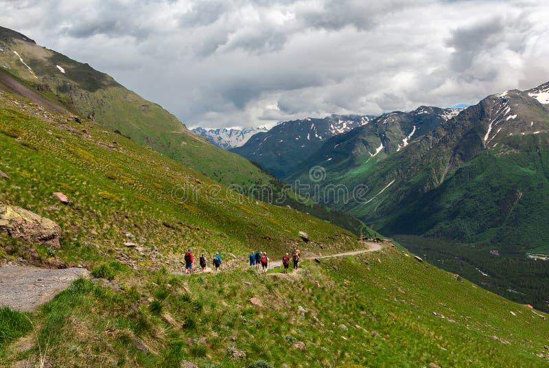 Le groupe de personnes hommes et les femmes marchent sur la gamme de montagne couverte d'herbe verte Jour ensoleill? chaud photo libre de droits