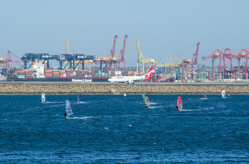 Le groupe de personnes joue la planche à voile avec l'avion de ligne aérienne de Qantas sur le port de piste et de cargaison à l' images libres de droits