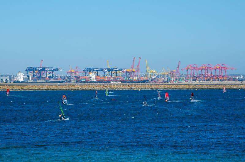 Le groupe de personnes joue la planche à voile avec le port de cargaison à l'arrière-plan, aux bains de plage de Kyeemagh image libre de droits