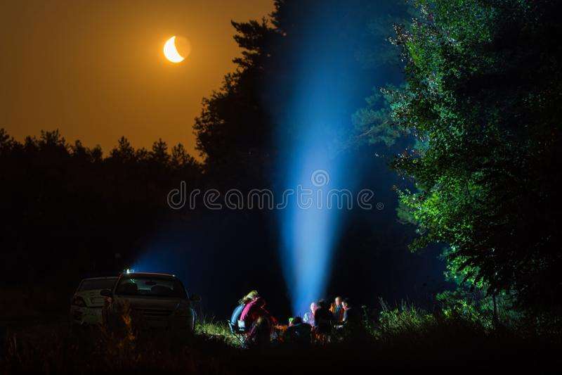 Le groupe de personnes s'asseyant autour du feu de camp photographie stock libre de droits