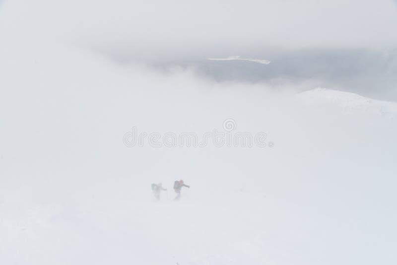 Le groupe de personnes trimardant en montagnes d'hiver pendant une neige fulminent, marchant au-dessus des nuages photos libres de droits