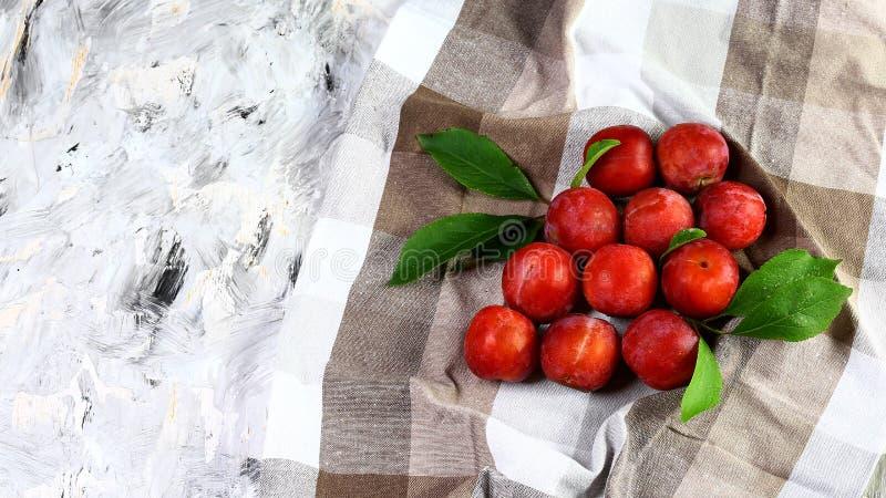 Le groupe de prunes mûres rouges avec le vert part sur une serviette de thé sur un fond clair Vue supérieure Copiez l'espace photos libres de droits