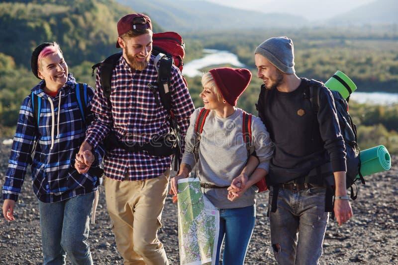 Le groupe de quatre voyageurs heureux marchent avec la carte et essayent de découvrir la bonne manière sur le dessus de montagne  image stock