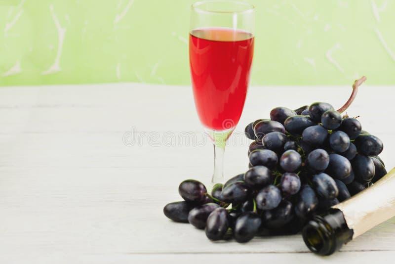 Le groupe de raisins bleus mûrs frais près de verre transparent et fragile complètement du vin et d'un a ouvert la bouteille sur  images libres de droits