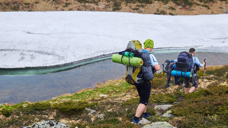 Le groupe de randonneurs marchant en montagnes photo stock