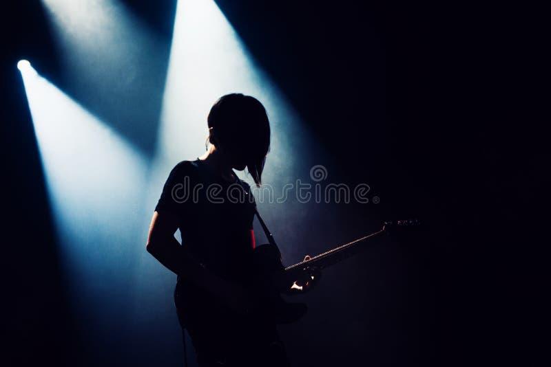 Le groupe de rock exécute sur l'étape Le guitariste joue solo Silhouette de joueur de guitare dans l'action sur l'étape devant la image stock