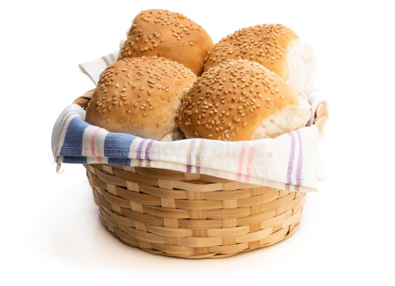 Le groupe de sésame a semé des petits pains d'hamburger dans le panier en osier d'isolement sur un blanc image libre de droits