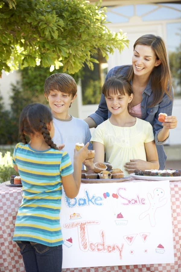 Le groupe de se tenir d'enfants font la vente cuire au four avec la mère images stock
