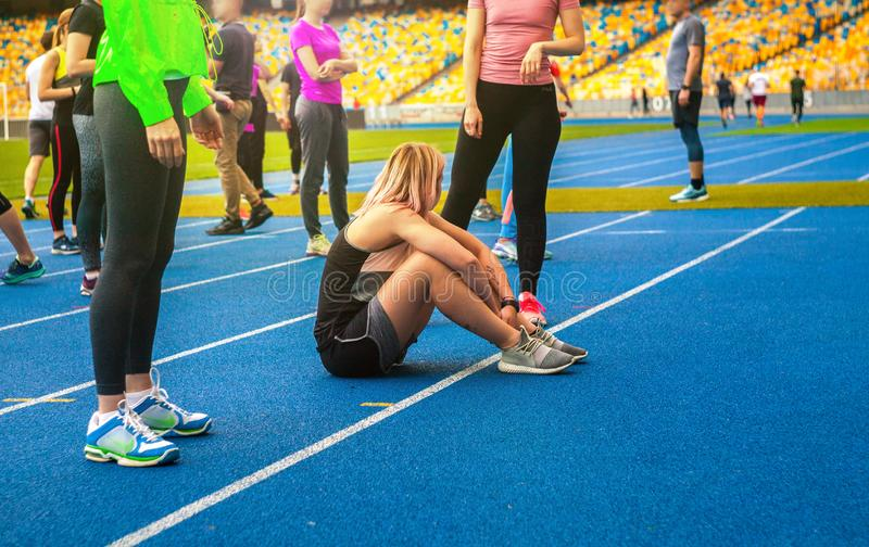 Le groupe de sportifs font les exersises sur le stade posture accroupie et bout droit image libre de droits