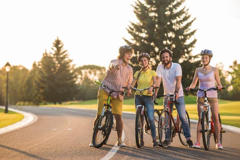 Le groupe des jeunes sur un vélo se déclenchent image libre de droits