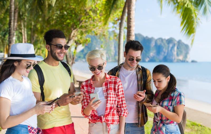Le groupe des jeunes utilisant la cellule Smart téléphone les amis tropicaux de palmiers de parc causant des vacances d'été en li photo libre de droits