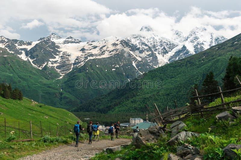 Le groupe divers d'hommes des jeunes et les femmes marchent sur le chemin de montagne au village images libres de droits