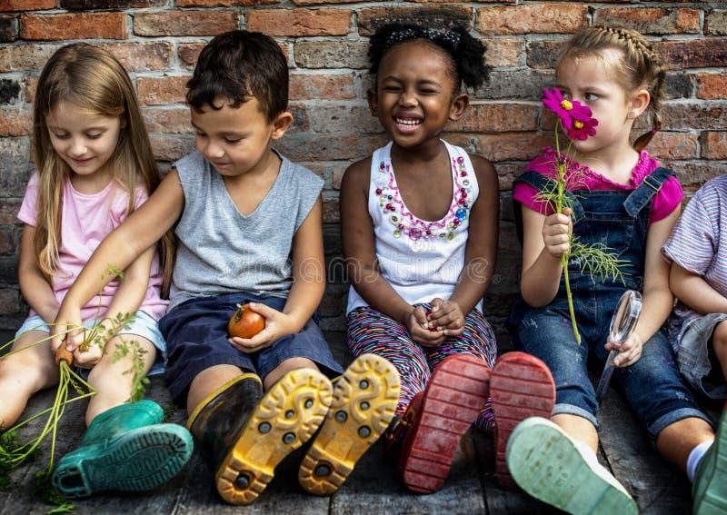 Le groupe du jardin d'enfants badine de petits agriculteurs apprenant le jardinage photographie stock