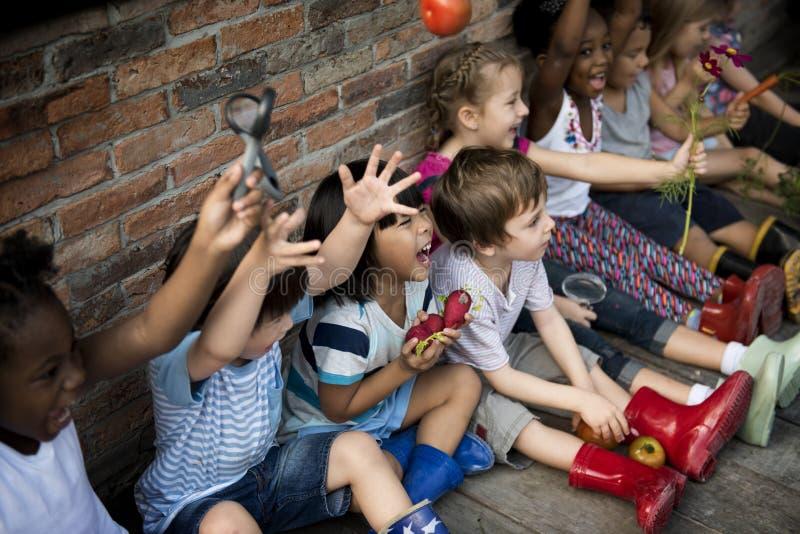 Le groupe du jardin d'enfants badine de petits agriculteurs apprenant le jardinage image stock