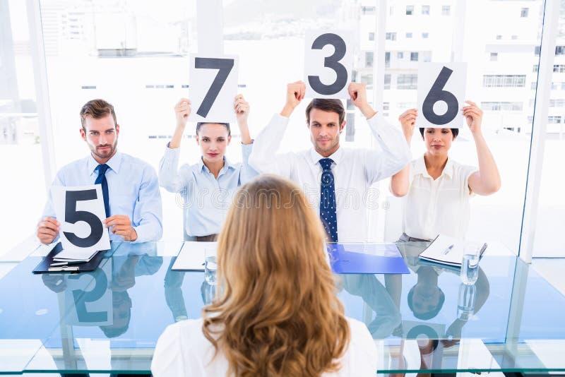 Le groupe du jury juge tenir des signes de score devant la femme images stock