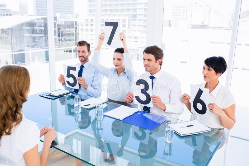 Le groupe du jury juge tenir des signes de score devant la femme photographie stock