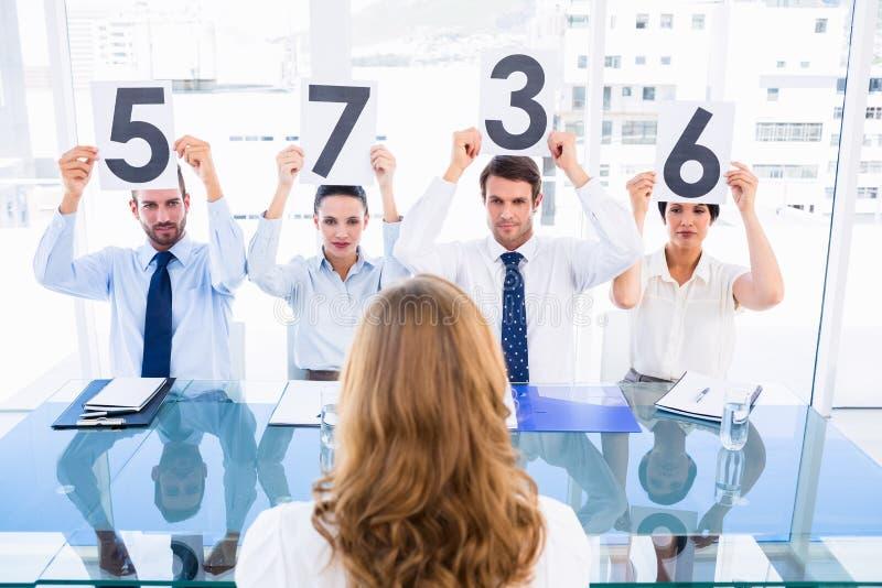 Le groupe du jury juge tenir des signes de score devant une femme photos stock