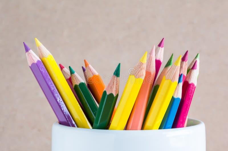 Le groupe du plan rapproché A de couleur crayonne dans une tasse blanche photographie stock