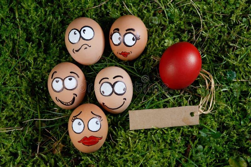 Le groupe du visage heureux eggs sur l'herbe verte image stock