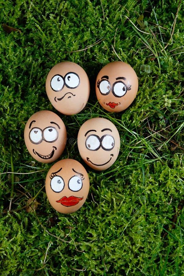 Le groupe du visage heureux eggs sur l'herbe verte photo stock