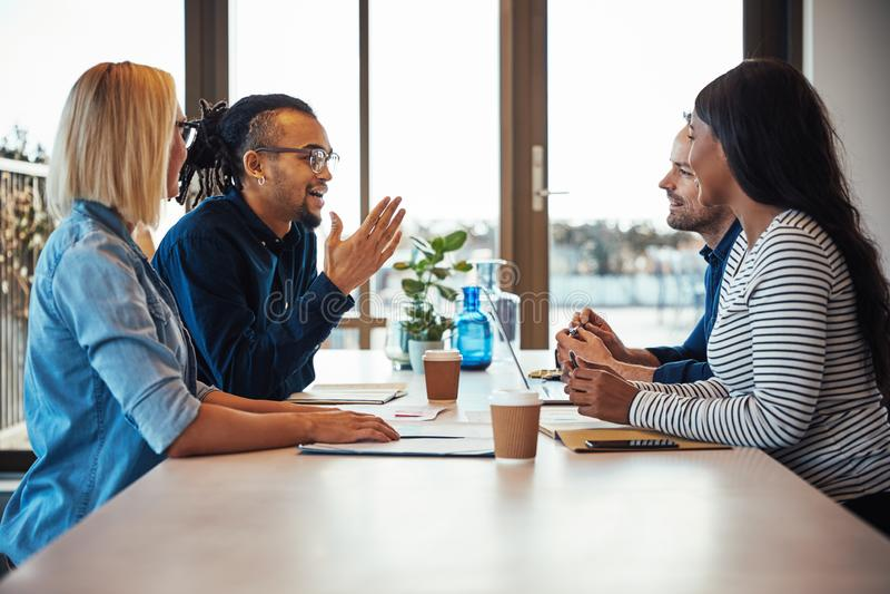 Le gruppen av kollegor som tillsammans talar runt om ett kontor de arkivfoton