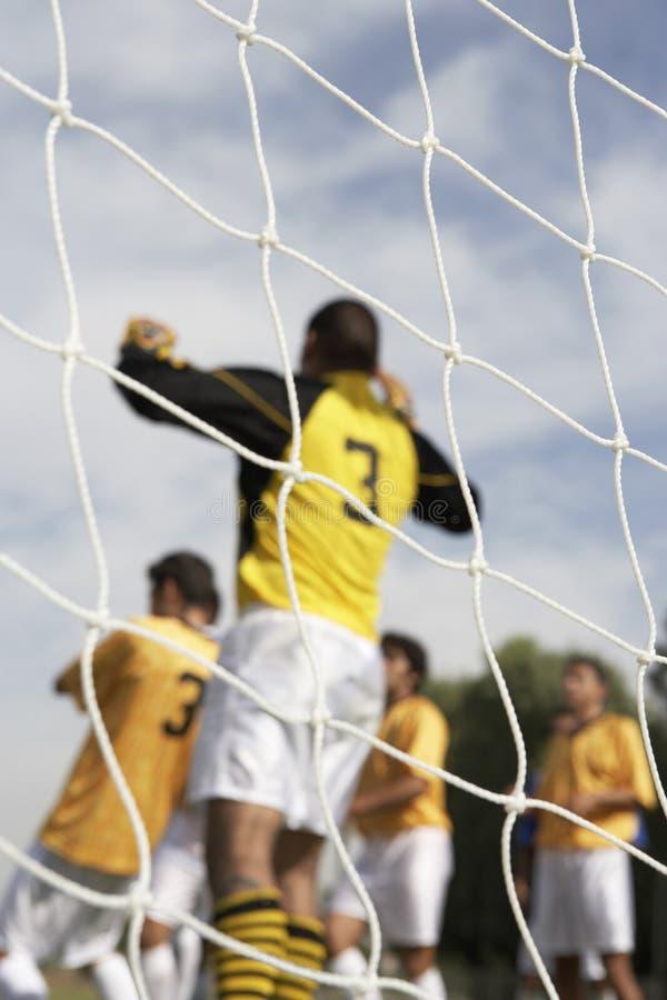 Le guardien de but sautant pour la bille de football photographie stock