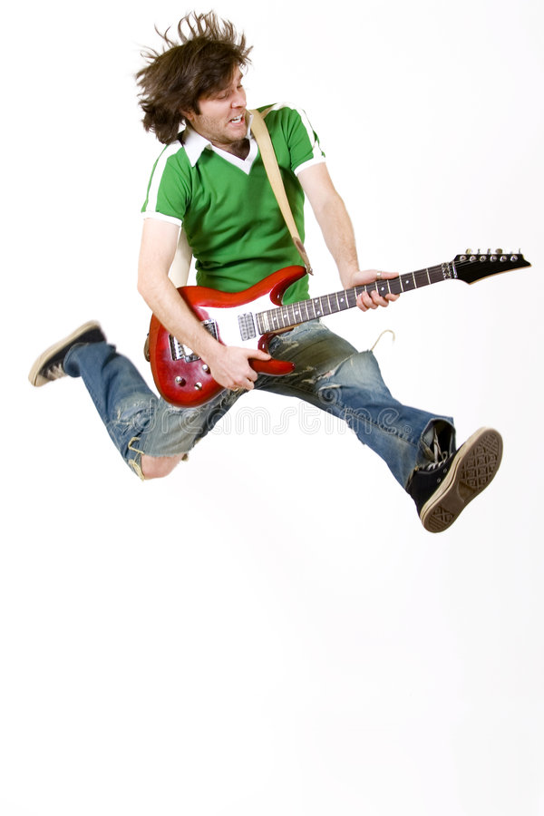 Le guitariste saute dans le ciel photo stock