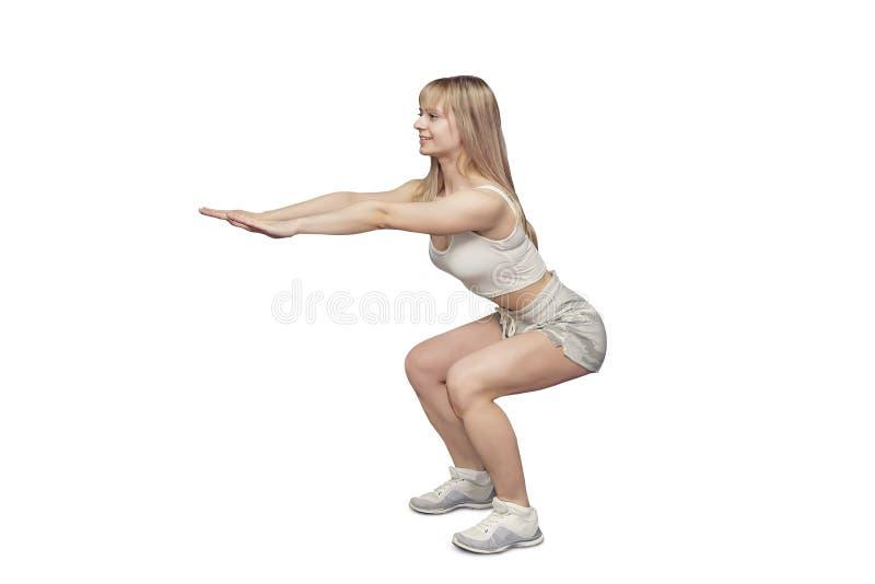 Le gymnaste blond folâtre dans les vêtements de sport s'accroupit sur le fond blanc dans le studio Pousse du côté Elle tient ses  images libres de droits