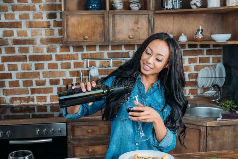 Le hällande vin för afrikansk amerikankvinna i exponeringsglas på kök arkivfoton