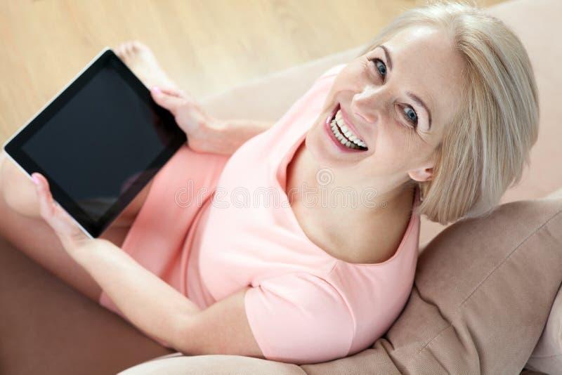 Le härligt medelålderst kvinnasammanträde på soffan med en minnestavla, med hänsyn till ny idé arkivfoton