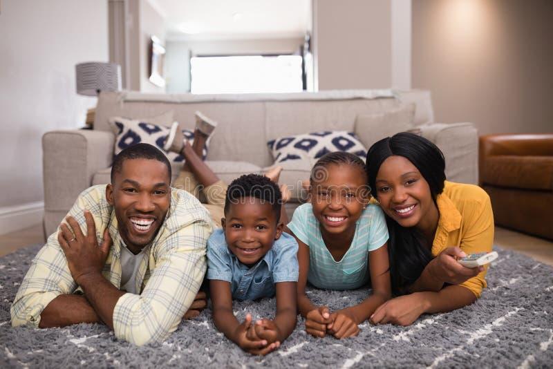 Le hållande ögonen på television för familj, medan ligga på filten hemma arkivbild