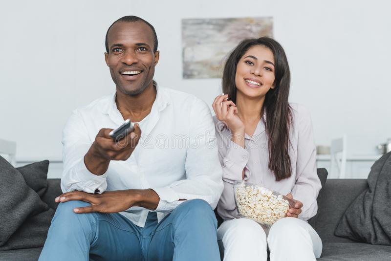 le hållande ögonen på tv för afrikansk amerikanpar med popcorn arkivfoton
