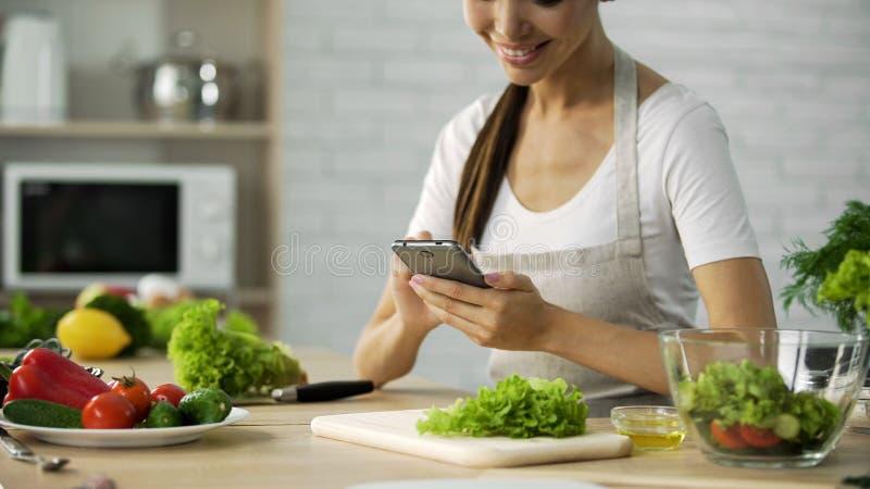 Le hållande ögonen på videopn recept för asiatisk flicka på smartphonen, innan att laga mat matställen arkivfoton