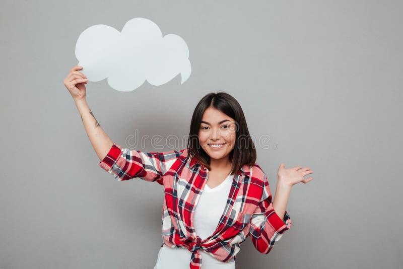Le hållande anförande för kvinna bubbla över den gråa väggen royaltyfria bilder