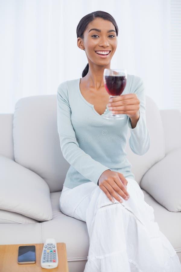 Le hållande exponeringsglas för attraktiv kvinna av rött vin arkivbild