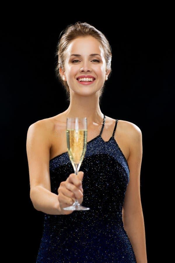 Le hållande exponeringsglas för kvinna av mousserande vin arkivfoto