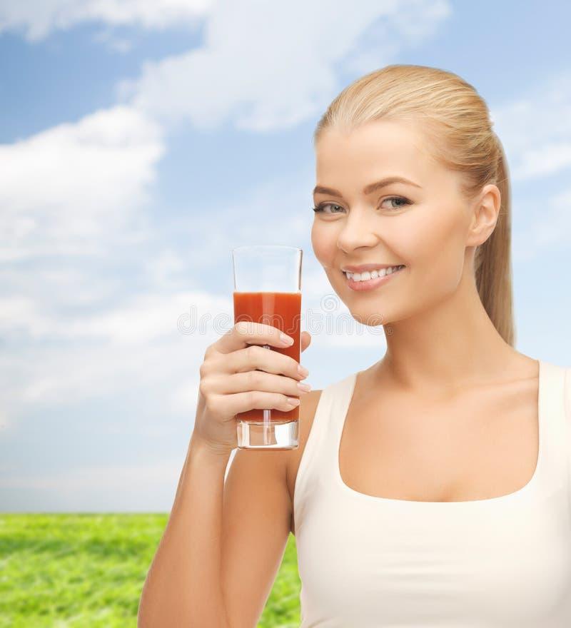 Le hållande exponeringsglas för kvinna av tomatfruktsaft arkivfoton