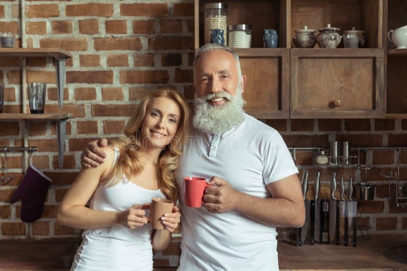 Le hållande kaffekoppar för par på kök royaltyfria foton