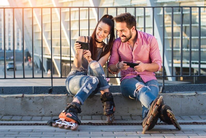 Le hållande mobiltelefoner för par arkivfoto