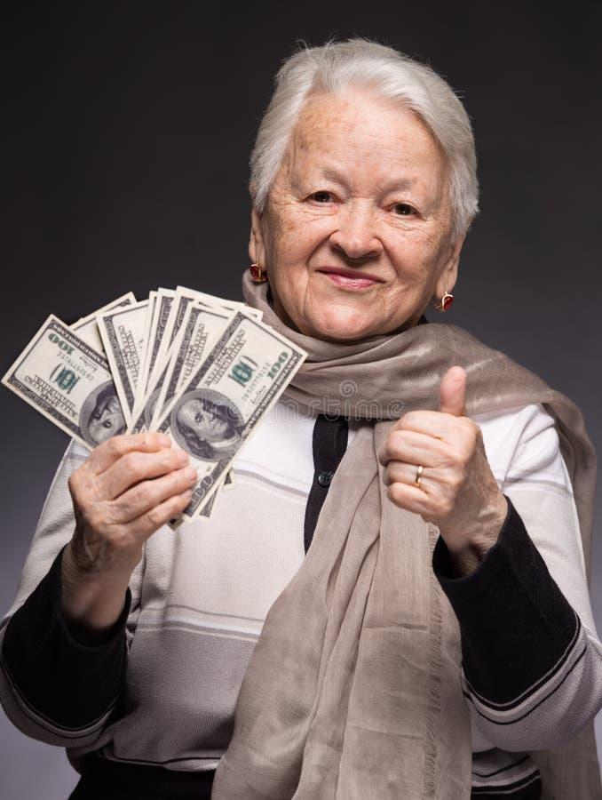 Le hållande pengar för gammal kvinna arkivfoton