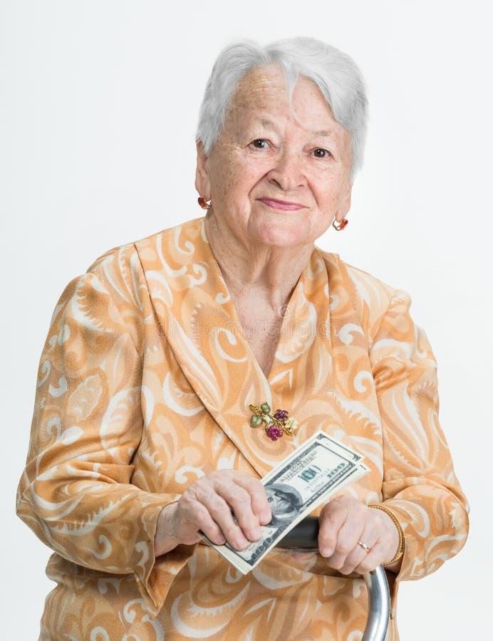 Le hållande pengar för gammal kvinna royaltyfri bild