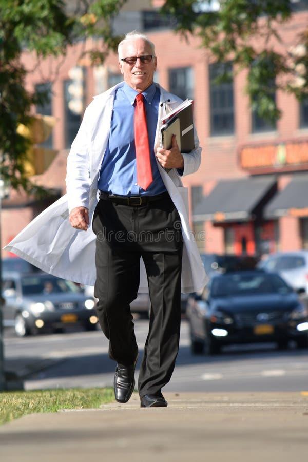 Le hög manlig doktor With Notebooks Walking royaltyfria bilder