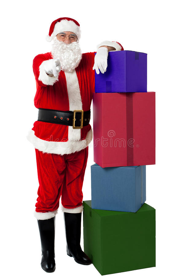 Le höga Santa som poserar bredvid färgrik bunt royaltyfri fotografi