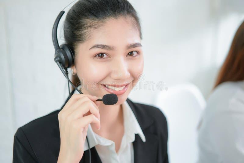 Le hörlurar med mikrofon för mikrofon för asiatisk affärskvinnakonsulent den bärande av operatören för telefon för kundservice på arkivbild